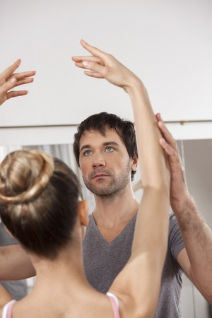 mid adult male: Mid adult male trainer teaching ballet to ballerina in studio
