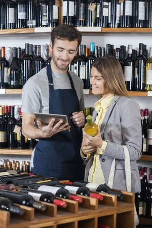 store keeper: Young salesman showing wine information to female customer on digital tablet in shop