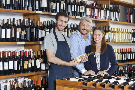 store keeper: Portrait of confident salesman holding wine bottle while standing with customers in shop