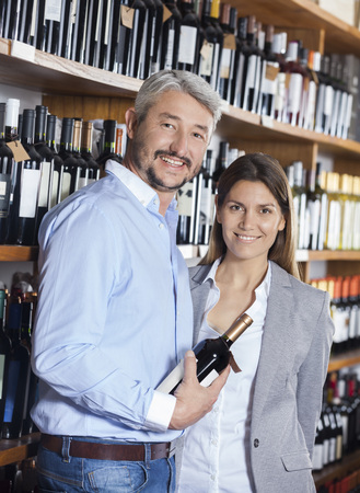 store keeper: Portrait of smiling couple with wine bottle in shop