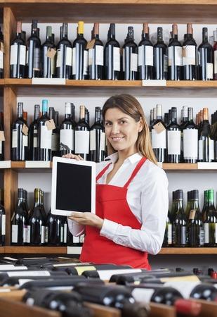 store keeper: Portrait of smiling saleswoman showing blank digital tablet in wine shop
