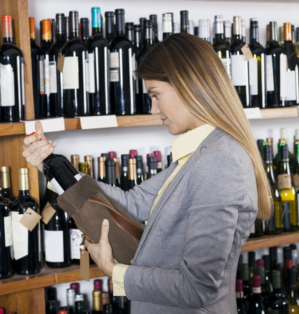 mid adult   female: Mid adult female customer removing wine bottle from bag in supermarket