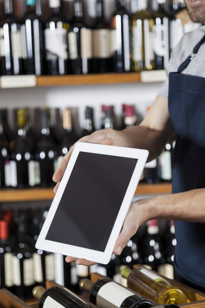 wine stocks: Midsection of salesman showing blank digital tablet in winery