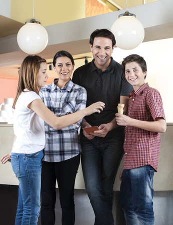 parlor: Portrait of happy family standing with girl in ice cream parlor Stock Photo