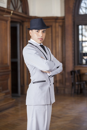 Portrait of confident tango dancer with arms crossed at restaurant Stock Photo