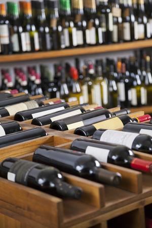 vertical: Wine bottles displayed on shelves and racks in supermarket