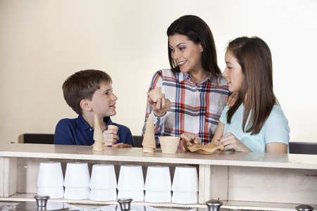 gelati: Smiling family choosing between cones and cups at counter in ice cream parlor