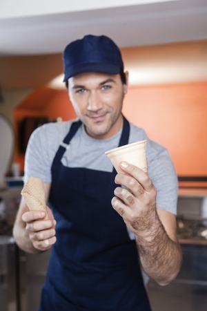 parlor: Portrait of confident waiter choosing between cup and cone at ice cream parlor Stock Photo