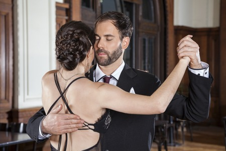 Romantic mid adult man closing eyes while performing tango with woman in restaurant