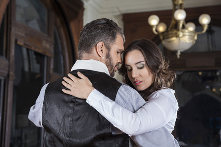 argentina dance: Shy young woman performing tango with man in restaurant