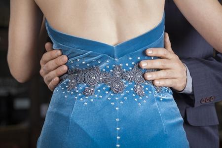 Sección media de hombre tocando la cintura de la mujer en el desempeño de tango en el restaurante
