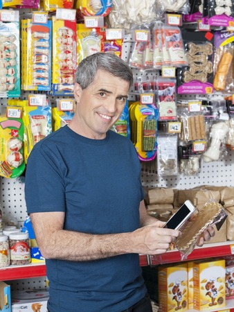 petshop: Portrait of confident male customer scanning pet product in store Stock Photo