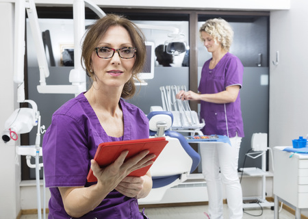 comunicacion oral: Portrait of assistant holding digital tablet while colleague working at dentistry