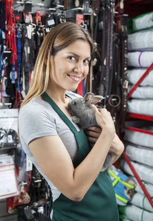 pet store: Portrait of smiling saleswoman holding rabbit at pet store