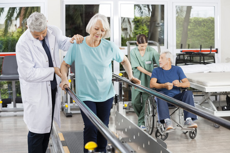 Mature doctor helping senior woman to walk between bars while physiotherapist pushing man in wheelchair at fitness center