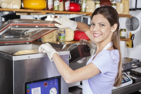 Portrait of smiling young saleswoman using vacuum packing machine in grocery store Foto de archivo