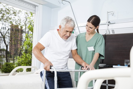 Young female nurse helping senior male patient in using walker at nursing home