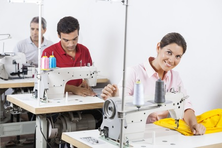 modiste: Smiling female tailor stitching fabric at sewing factory with colleagues in background Stock Photo