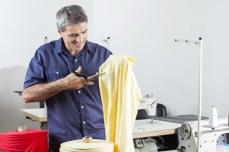 modiste: Mature male tailor cutting yellow textile while standing at sewing factory Stock Photo