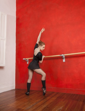 ballet bar: Full length of young female ballet dancer performing at barre against red wall in studio
