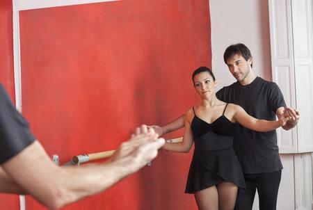 ballet hombres: Macho maestro de la bailarina de guía en frente del espejo en el estudio de ballet Foto de archivo