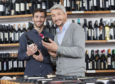 Portrait of smiling male friends holding wine bottles in shop