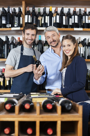 shop keeper: Portrait of confident couple and salesman with wine bottle in shop