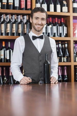 store keeper: Portrait of confident bartender with wine bottle standing at counter in winery Stock Photo