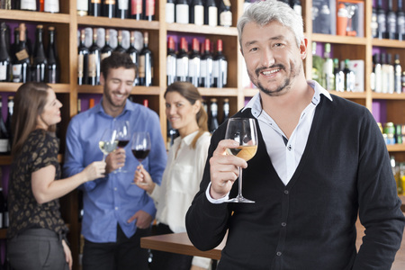 store keeper: Portrait of happy mature man holding wineglass with friends in background at shop