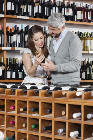 copule: Smiling couple with wine bottle standing at rack in shop