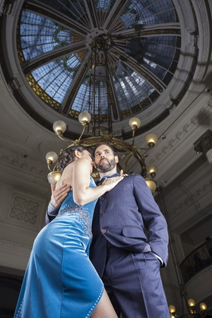 angle bar: Low angle view of mid adult tango dancers standing below cupola in restaurant
