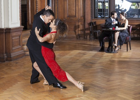 Confident tango dancers performing while mid adult couple dating in restaurant