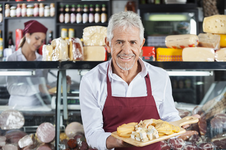 Portrait of smiling salesman holding various cheese on cutting board with colleague in background at store Stock Photo