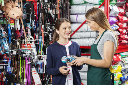 petshop: Happy girl looking at saleswoman while buying toy in pet store Stock Photo