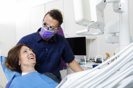 mid adult male: Mid adult male dentist examining happy female patient in clinic