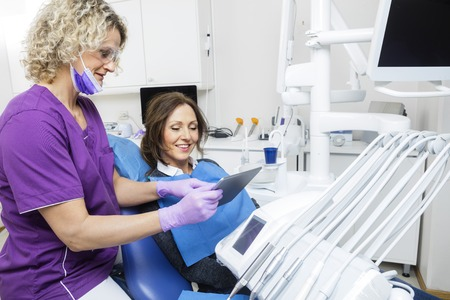 oral communication: Female assistant showing report to patient on tablet computer in dentistry Stock Photo