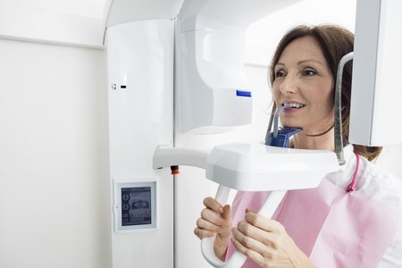 Closeup of female patient using digital panoramic xray machine while looking away in clinic Stock Photo - 61273912