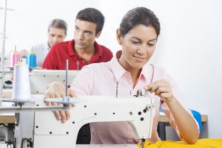 Souriant tailleur féminin réglage machine à coudre à l'usine avec des collègues en arrière-plan
