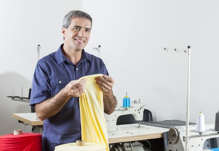 modiste: Thoughtful mature male tailor holding yellow fabric while smiling at sewing factory