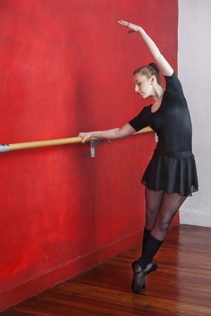 dance bar: Full length of young ballerina practicing at wall bar in dance studio