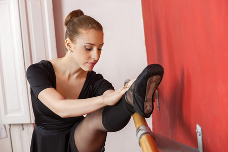 barre: Portrait of young ballerina stretching her leg at barre in dance studio