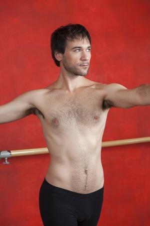 ballet hombres: Sin camisa bailarina de ballet masculino practicando contra la pared roja en el estudio de baile Foto de archivo
