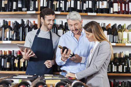 store keeper: Multiethnic couple reading label on wine bottle while standing by salesman holding digital tablet in store