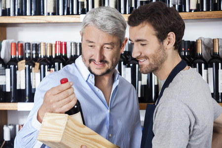store keeper: Smiling male customer and salesman looking at wine bottle in shop Stock Photo