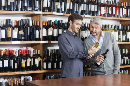 liquors: Multi ethnic male friends reading label of wine bottles in shop