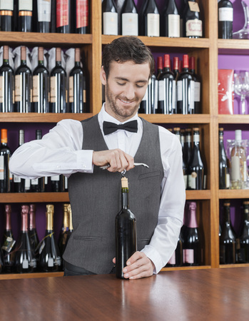 shop keeper: Smiling bartender opening wine bottle at counter in winery