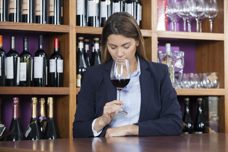shop keeper: Mid adult female customer smelling red wine at counter in shop Stock Photo