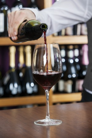 store keeper: Cropped image of male bartender pouring red wine in glass at counter