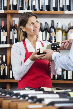 shop keeper: Smiling saleswoman giving wine bottle to male customer in shop