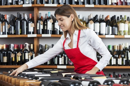 arranging: Mid adult saleswoman arranging wine bottles in rack at winery Stock Photo